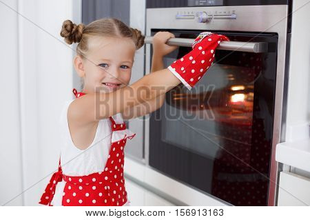 Little housewife blonde girl is 5 years old,his hair neatly gathered,dressed in a white vest and a red apron with white polka dots,bakes muffins in colorful shapes in a large oven,working alone at home in the bright kitchen in red mitten