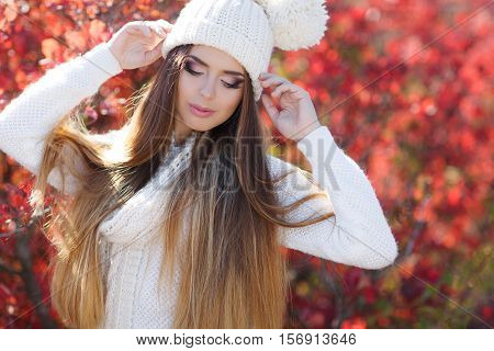 Beautiful young woman in white knitted sweater and white knit cap,brunette,long straight hair,drooping eyelids with long eyelashes,pink lipstick posing in autumn Park on a background of red,yellow and green leaves,portrait in autumn Park