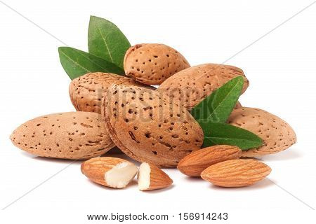 heap of almonds in their skins and peeled with leaf isolated on white background.