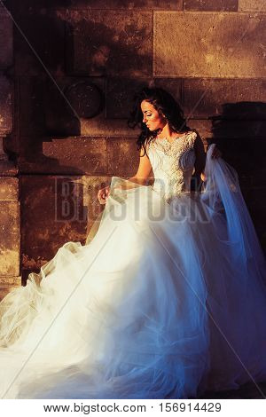 Young bride woman brunette with pretty face in splendid wedding white dress posing on dark stone wall background at night outdoor