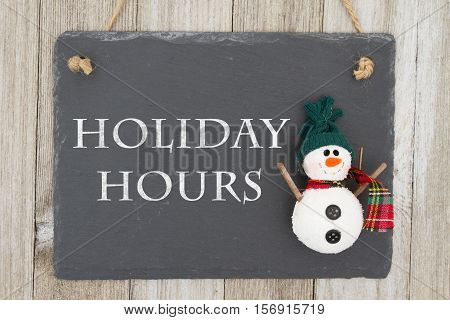 Old fashion Christmas store message A retro chalkboard with a snowman hanging on weathered wood background with text Holiday Hours