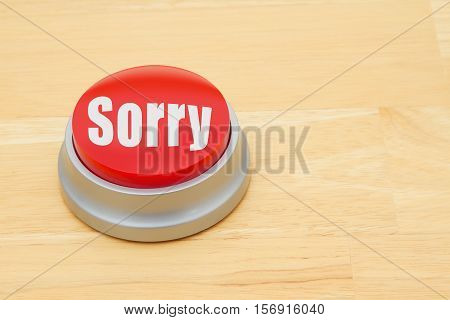 A Sorry red push button A red and silver push button on a wooden desk with text Sorry