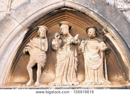 DUBROVNIK, CROATIA - NOVEMBER 30: Jesus Christ, St. John the Baptist and St. Nicholas with a stick, portal of Saint Luke Church in Dubrovnik, Croatia on November 30, 2015.