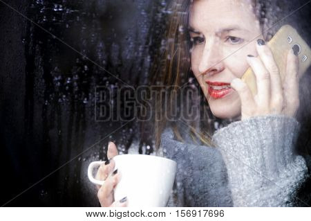 attractive adult woman drinking coffee speaking with mobile and looking out of the window on rainy day, close up portre in winter time