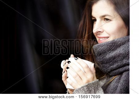 attractive adult woman drinking coffee and looking out of the window on cold day, close up portre in winter time