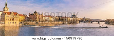 Vltava river and buildings in Prague - Panorama view with the buildings of Prague the capital of Czech Republic and the Vltava river on a sunny day of spring.