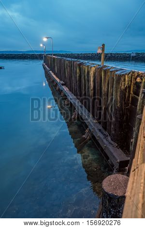 A wall of wooden posts juts out at Des Moines Marina as darkness falls.