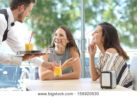 Happy casual friends meeting in a bar with a window with green outdoors in the background and the waiter serving refreshments