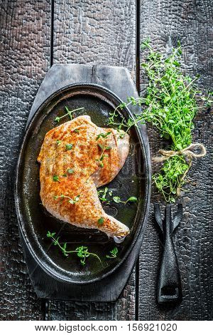 Piece Of Chicken With Fresh Marjoram On Black Burning Table