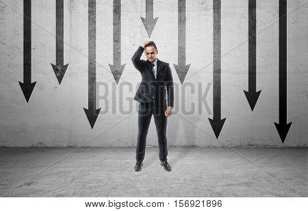 A sad businessman in a frustrated pose, standing on the background of many black arrows pointing down, painted on a grey wall. Business and management. Failures and problems. Poses and gesrures.