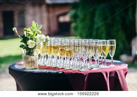 Glasses with champagne on a beautiful black table, in the Park in the summer. Sunny weather.