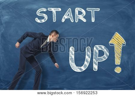 A businessman standing as if he is going to run near the phrase 'start up' written on the dark blue wall. Beginning of career. Starting business. Young entrepreneur.
