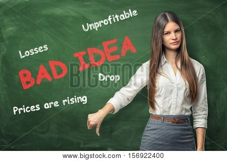 A young woman giving thumbs down gesture standing near the big red words 'bad idea' and the other negative words written on the green wall. Bad business decisions. Social and economic problems. To bear losses.