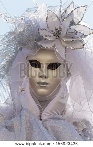 Venice, Italy - February 16, 2015: Close up of a model disguised in a bright Venetian costume posing during the Carnival of Venice