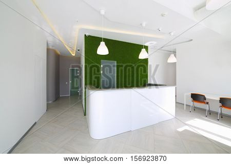 Empty light reception room with desk, green lawn wall in business center