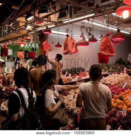 HONG KONG - October 2016: People shopping at fruit stall on wet market.