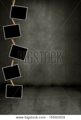 Blank photos hanging vertically in a dark grungy room
