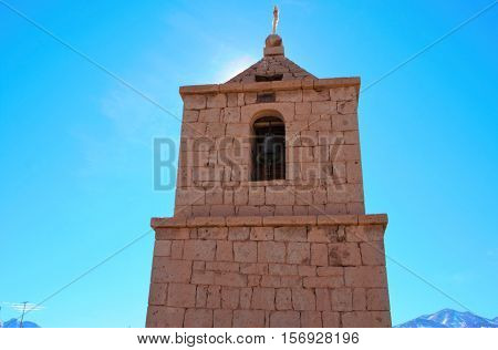 Low angle view of the old church in Socaire made out of bricks with a blue sunny sky close to San Pedro de Atacama in Chile South America