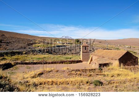 Long shot of the old church in Socaire made out of bricks and its surroundings with a blue sunny sky close to San Pedro de Atacama in Chile South America