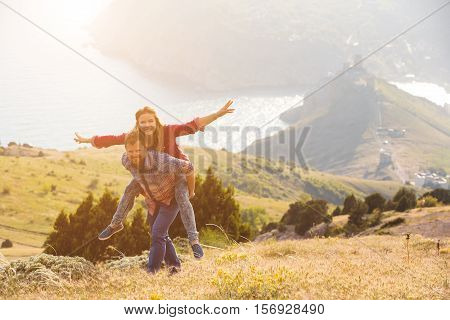 Beautiful loving couple in hipster fashion style posing on mountain