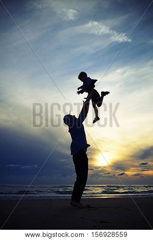 Mid low angle shot of the dad silhouette tossing up a child at the sunset while standing on the beach