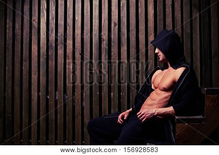 Side view of the brawny thoughtful model who is sitting on wooden stairs wearing a black hood. Showing his reliefed body