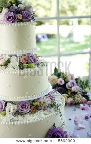 An ivory wedding cake with roses in the window