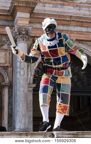 VENICE, ITALY - FEBRUARY 16, 2015: Harlequin mask in San Marco square during Venice carnival