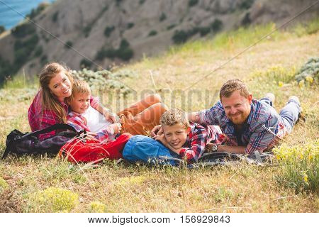 happy family of four people looking to beautiful seascape in mountains. family concept