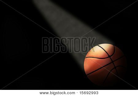 A dramatically lit basketball on the court