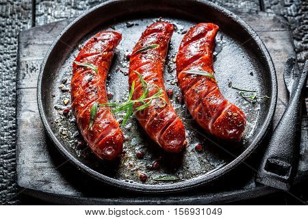 Grilled Sausage With Fresh Herbs On Black Burnt Table