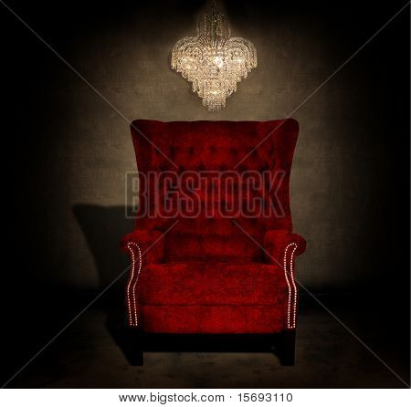 Crystal chandelier hanging in a dark grungy room with an antique red chair