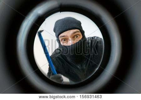 View Through Pipehole. Thief Or Burglar Masked With Balaclava Is