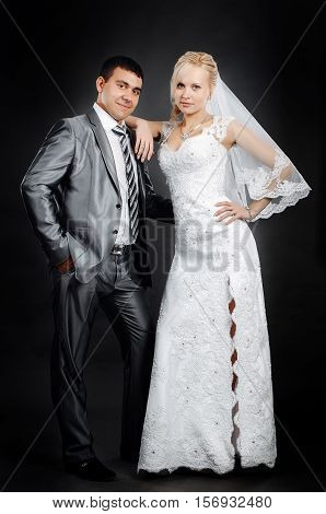 Loving newlyweds standing on a gray background
