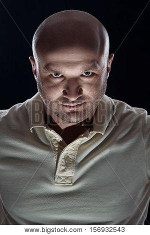 brutal portrait of a bald man bristles on a black background