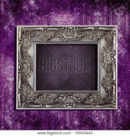 Intricate old frame hanging on grungy violet vintage wallpaper