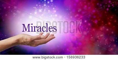 Asking for Miracles background - female hand facing up with the word MIRACLES floating in a white sparkling oval on a deep pink background with glittering sparkles and copy space to right side