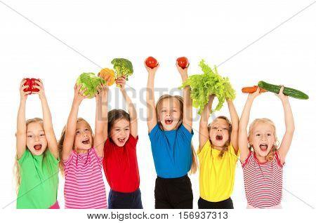 Group of little girls holding vegetables isolated on white