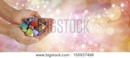 Crystal Therapist Sparkling Website Banner - female crystal therapist holding and offering a  selection of crystals on a wide sparkling orange background