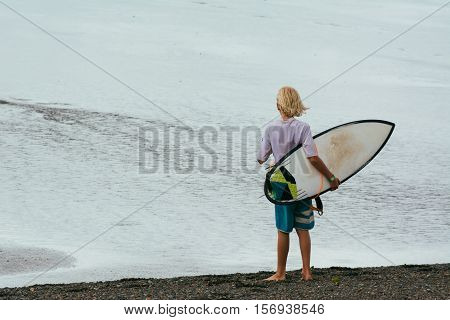 Young surfer holding his surfboard. On his back.