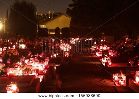 A night view of ornated graves with flowers and burning lampions at cemetery on All Saints day in Velika Gorica Croatia.