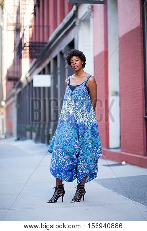 Young fashionable African American woman in blue dress on city street. Photographed in Soho New York City.