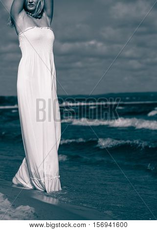 Rest and relax concept. Attractive gorgeous blonde woman wearing white dress resting on fresh air on beach seaside. Summer time.