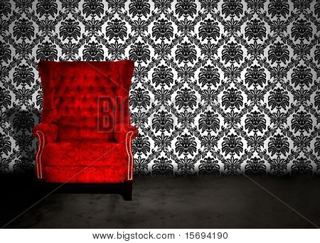 A red velvet chair in a dark room with antique wallpaper