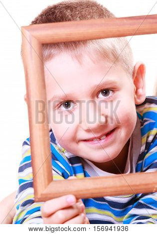 Spending free time and have fun. Playful little boy play with empty picture frame show face hold.