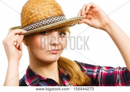Gardening concept. Attractive woman in dungarees pink check shirt holding sun hat on head. Isolated background