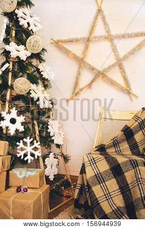 Christmas photo zone in vintage style with hand-made Christmas tree and chair with a blanket