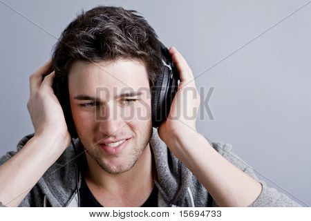 Attractive guy holding headphones listening to music