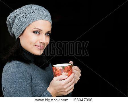 Beautiful girl drinking tea or coffee on black background