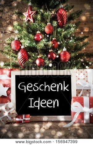 Chalkboard With German Text Geschenk Ideen Means Gift Ideas. Christmas Card For Seasons Greetings. Christmas Tree With Balls. Gifts Or Presents In The Front Of Wooden Background.
